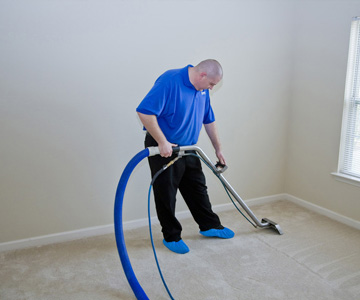 Man hoovering a carpet