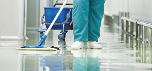 Person mopping a corridor in a healthcare building